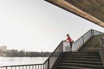 Giovane donna che si estende sulle scale di un fiume in città — Foto stock