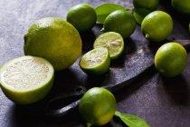 Свежие цельные и наполовину сочные лаймы и фрукты Помело на темном фоне гранжа — стоковое фото