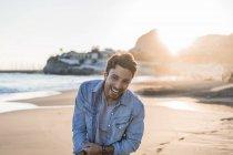 Портрет смеющегося молодого человека на пляже на закате — стоковое фото