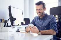 Lächelnder Mann mit Handy am Schreibtisch im Büro — Stockfoto