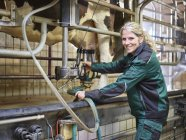 Portrait of smiling female farmer in stable milking a cow — Stock Photo