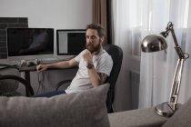Retrato de homem barbudo sentado na sala e ouvindo música com fones de ouvido — Fotografia de Stock