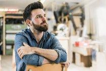 Мужчина сидит на стуле в мастерской — стоковое фото
