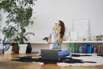 Jovem em casa sentada no chão e conversando no celular — Fotografia de Stock