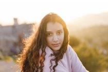 Porträt einer jungen Frau mit langen lockigen Haaren bei Sonnenuntergang — Stockfoto