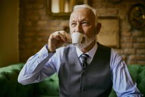 Elegant senior man drinking coffee in a cafe — Stock Photo