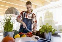 Беременная женщина на кухне дома режет огурец — стоковое фото