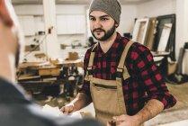 Arbeiter schaut Kollegin in Werkstatt an — Stockfoto