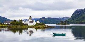 Reino Unido, Escocia, Costa Oeste, Plockton, Loch Carron, casas residenciales y barco - foto de stock