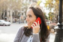 Smiling woman on cell phone in the city — Stock Photo