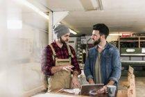 Двоє чоловіків з планшетом обговорюють в майстерні — стокове фото