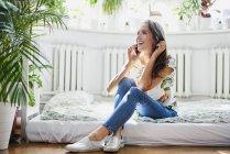 Счастливая молодая женщина разговаривает по телефону дома — стоковое фото
