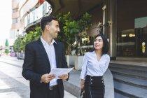 Tailândia, Banguecoque, homem de negócios e mulher de negócios de sorriso com os originais que falam na cidade — Fotografia de Stock