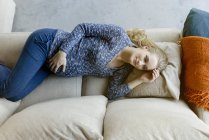 Pregnant woman lying on couch at home — Stock Photo