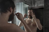 Portrait d'homme barbu regardant son image miroir tout en tournant sa barbe — Photo de stock