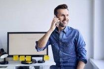 Sorrindo homem na mesa no escritório falando ao telefone — Fotografia de Stock
