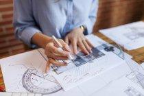 Молодая женщина, работающая в архитектурном бюро, рисует чертежи — стоковое фото