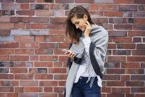 Jeune femme souriante regardant le téléphone cellulaire devant un mur de briques — Photo de stock