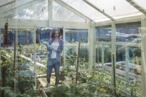 Sorridente giovane donna in piedi in una serra — Foto stock