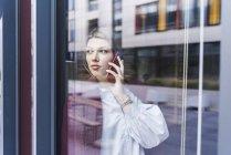 Jeune femme sur téléphone portable derrière le panneau de fenêtre — Photo de stock