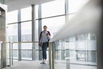 Девушка, стоящая у окна и пользующаяся мобильным телефоном — стоковое фото