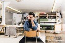 Homem sentado na cadeira na oficina — Fotografia de Stock