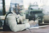 Улыбающийся молодой человек в кафе смотрит на мобильный телефон — стоковое фото
