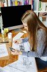 Giovane donna che lavora nello studio di architettura, utilizzando il telefono — Foto stock