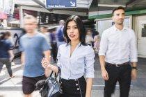 Таиланд, Бангкок, портрет бизнес-леди среди движущихся людей в городе — стоковое фото