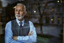 Елегантний старший чоловік, дивлячись з вікна — стокове фото