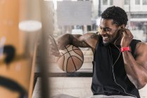 Улыбающийся африканский американец с татуировками и баскетбольным мячом с помощью смартфона и наушников — стоковое фото