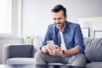 Smiling man sitting on sofa and using cell phone — Stock Photo