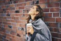 Mulher feliz com café para ir na frente da parede de tijolo — Fotografia de Stock