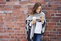 Femme heureuse avec du café pour aller regarder le téléphone cellulaire en face du mur de briques — Photo de stock