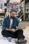 Кузнец с ноутбуком и строительным планом сидит на полу — стоковое фото