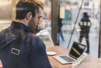 Joven hombre de negocios en un café en la estación de tren con teléfono celular, beber café de la taza - foto de stock