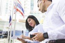 Таиланд, Бангкок, бизнесмен и деловая женщина в городе с документами, мобильный телефон и смартфоны — стоковое фото