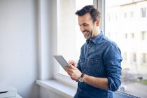 Smiling man using tablet at the window — Stock Photo