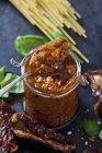 Spoon and glass of tomato pesto — Stock Photo