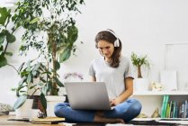 Молодая женщина сидит дома на полу, используя ноутбук и слушая музыку — стоковое фото