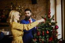 Elegante pareja decorando el árbol de Navidad - foto de stock
