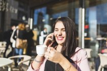 Ridere giovane donna d'affari sul cellulare in un caffè all'aperto — Foto stock