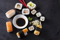 Variety of sushi with wasabi, ginger and bowl of soy sauce on dark ground — Stock Photo