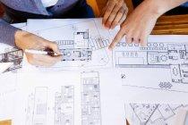 Команда архитекторов, работающих над проектом, обсуждающих чертежи — стоковое фото