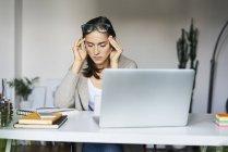 Молодая женщина дома с ноутбуком на столе трогает виски — стоковое фото
