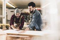 Dos hombres discutiendo en taller - foto de stock