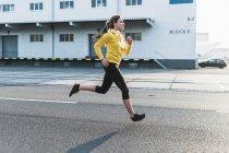 Молода жінка біжить по вулиці. — стокове фото