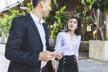 Thailandia, Bangkok, uomo d'affari sorridente e donna d'affari con documenti che parlano in città — Foto stock