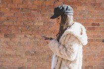 Jeune femme élégante devant un mur de briques et en utilisant un téléphone portable — Photo de stock