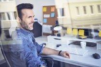 Sorrindo homem olhando através da janela no escritório enquanto sentado na mesa — Fotografia de Stock